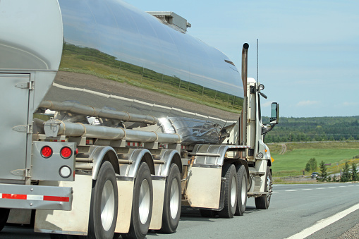 Rear quarter view of a semi tanker truck on a highway hauling milk to a dairy.