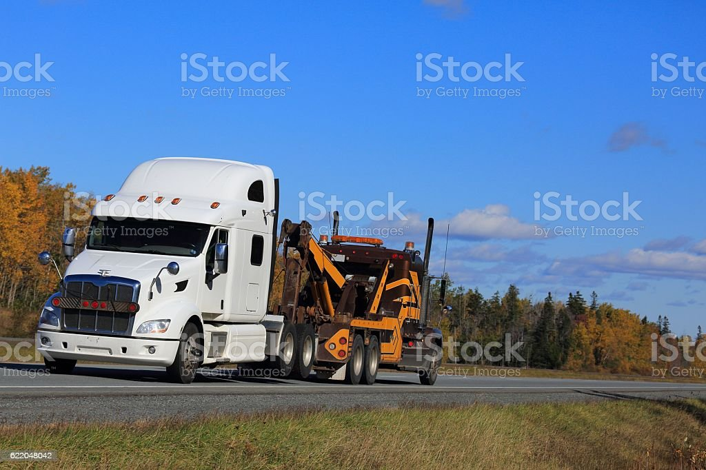 Semi tow truck hauling a semi truck, trees in background. stock photo