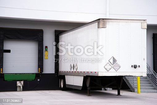 Semi trailer for freight in American logistic system big rigs semi trucks loading cargo at warehouse dock with thermally insulated gate to minimize temperature change of the load when loading