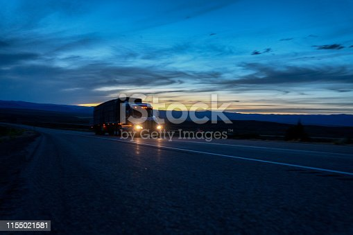 A semi-truck with headlights shining in the dark, driving on I-70 in Western Colorado at night