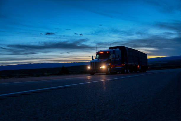 A Semi Trailer Truck Driving Down The Highway In Colorado At Night stock photo