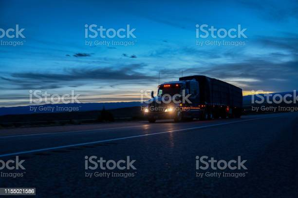 Photo of A Semi Trailer Truck Driving Down The Highway In Colorado At Night