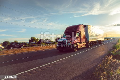 A semi-truck driving on I-70 in Western Colorado around sunset