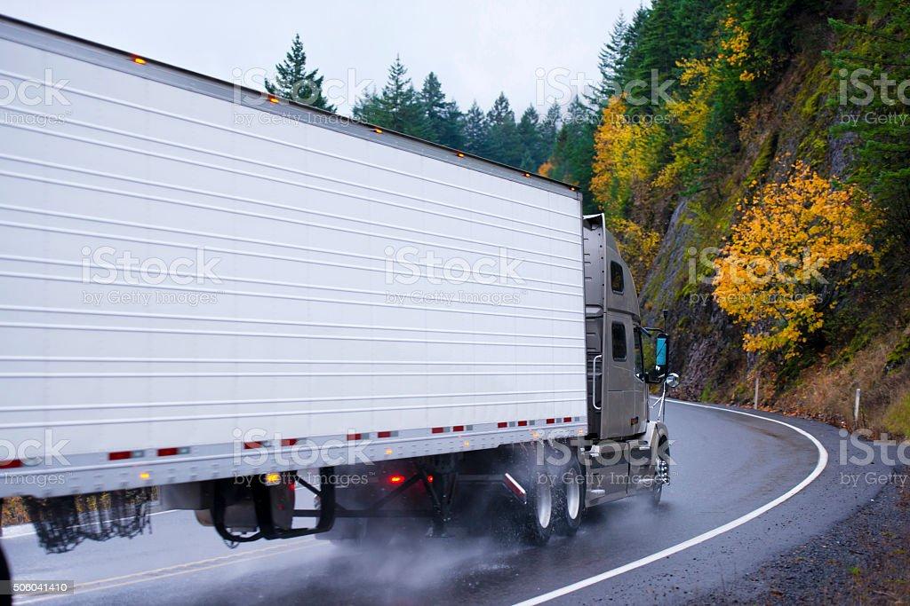 Semi truck and reefer trailer wheels in autumn rain dust stock photo