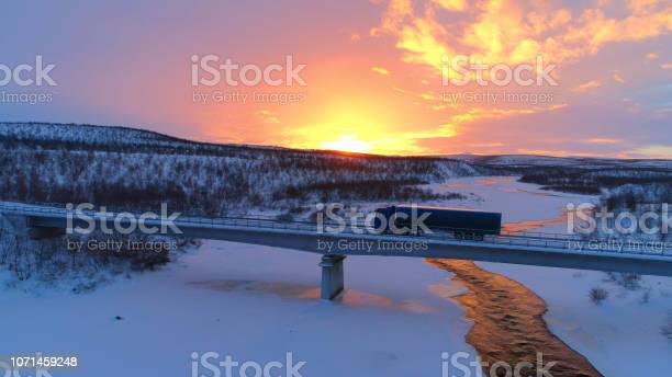 Photo of AERIAL: Semi truck crossing the bridge above icy river in the winter at sunset