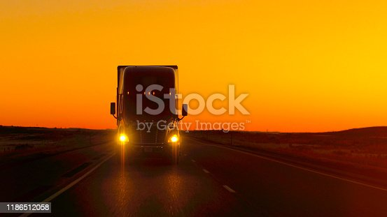CLOSE UP LENS FLARE: Semi truck driving and hauling goods on empty highway across the Great Plains in golden morning. Freight delivery truck transporting cargo on interstate freeway at stunning sunset