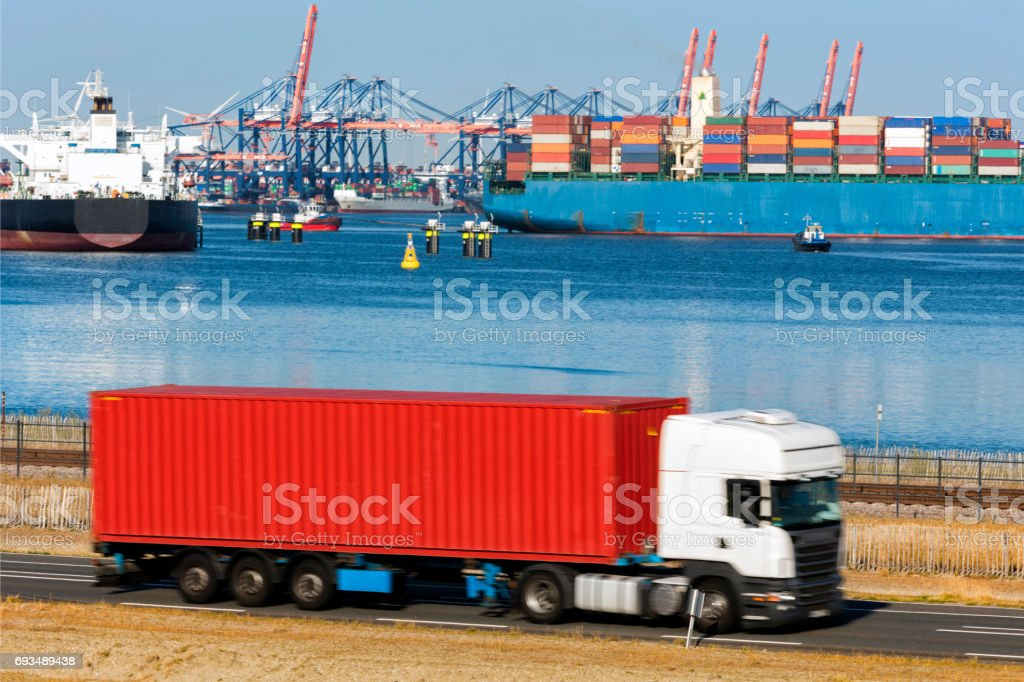 Semi Truck Driving on Road in Front of Harbor, Blurred Motion stock photo
