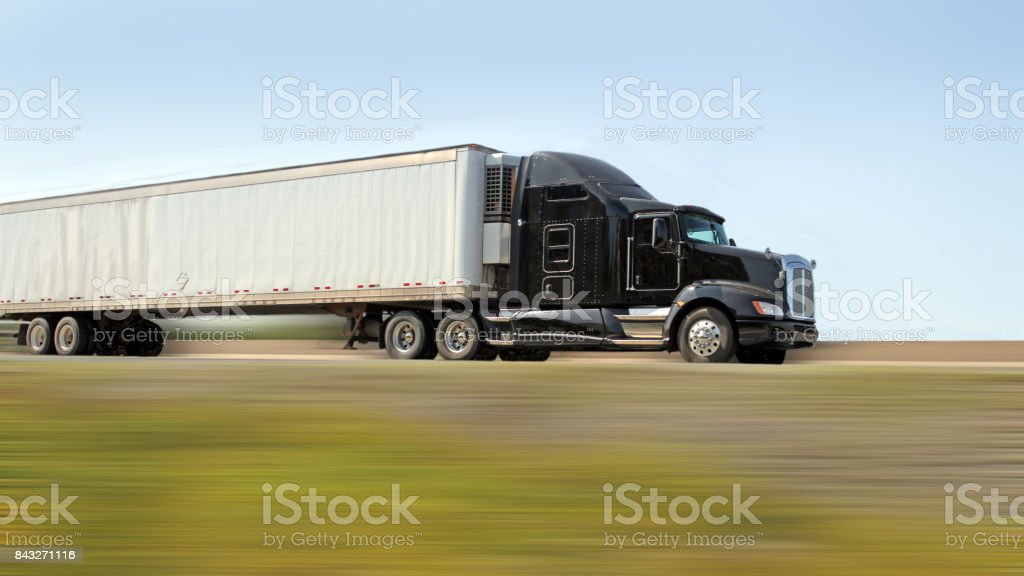 Semi Truck Hauling Freight, Blurred Foreground, 16x9 Format stock photo