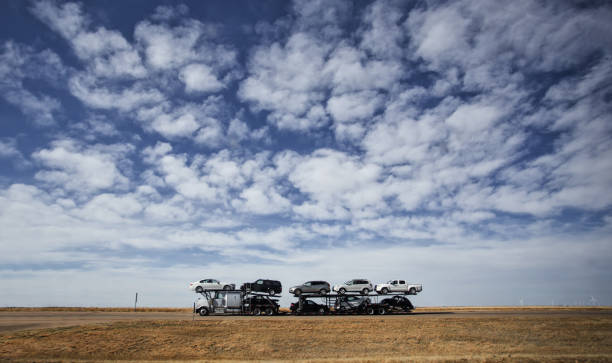 Semi truck hauling vehicles A semi truck hauling a load of dealership vehicles down an interstate under blue cloudy sky in a Wyoming countryside landscape carrying stock pictures, royalty-free photos & images