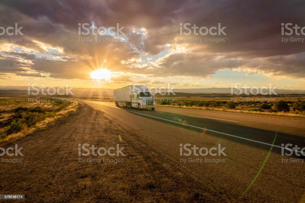 Semi Truck Heading East Bound With a Beautiful Sunset stock photo