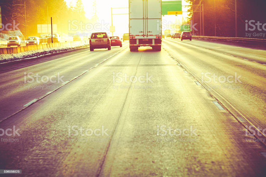 Semi Truck & Other Traffic Driving Freeway Toward Sunset stock photo