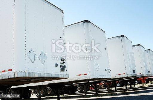 Row of white semi truck trailers on a clear blue sky. Check my transportation lightbox for more trucks.