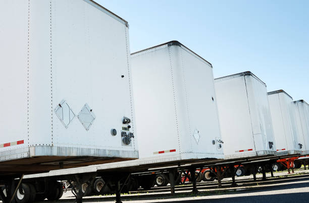Semi truck trailers Row of white semi truck trailers on a clear blue sky. Check my transportation lightbox for more trucks. vehicle trailer stock pictures, royalty-free photos & images