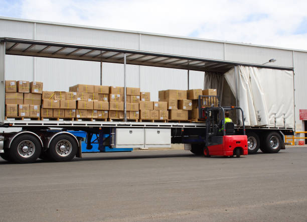 semi truck with forklift driver unloading - lorries unloading stock photos and pictures