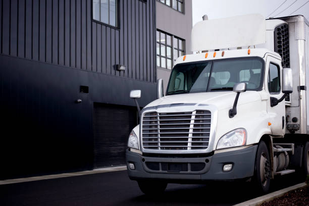 semi truck with refrigerator trailer unloading cargo at warehouse parking. - lorries unloading stock photos and pictures
