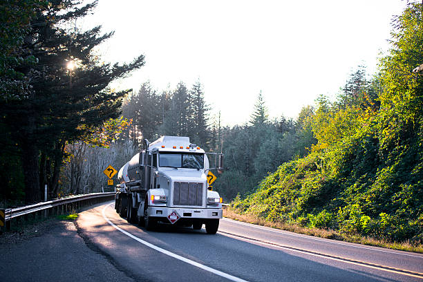 semi truck with tank trailers on winding road in forest - aufgemotzte trucks stock-fotos und bilder
