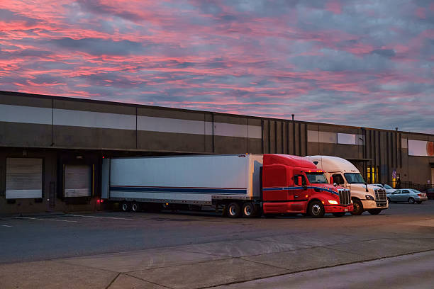 Semi trucks at freight dock at dawn stock photo
