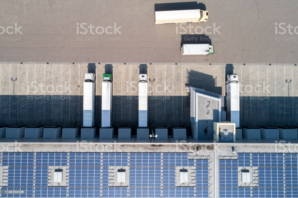 Semi Trucks at Warehouse, Aerial View Aerial view of semi trucks during unloading and a large storehouse with solar panels on the rooftop. Aerial View Stock Photo