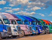 semi trucks in rainbow of colors, rainbow of colors, new truck in a row