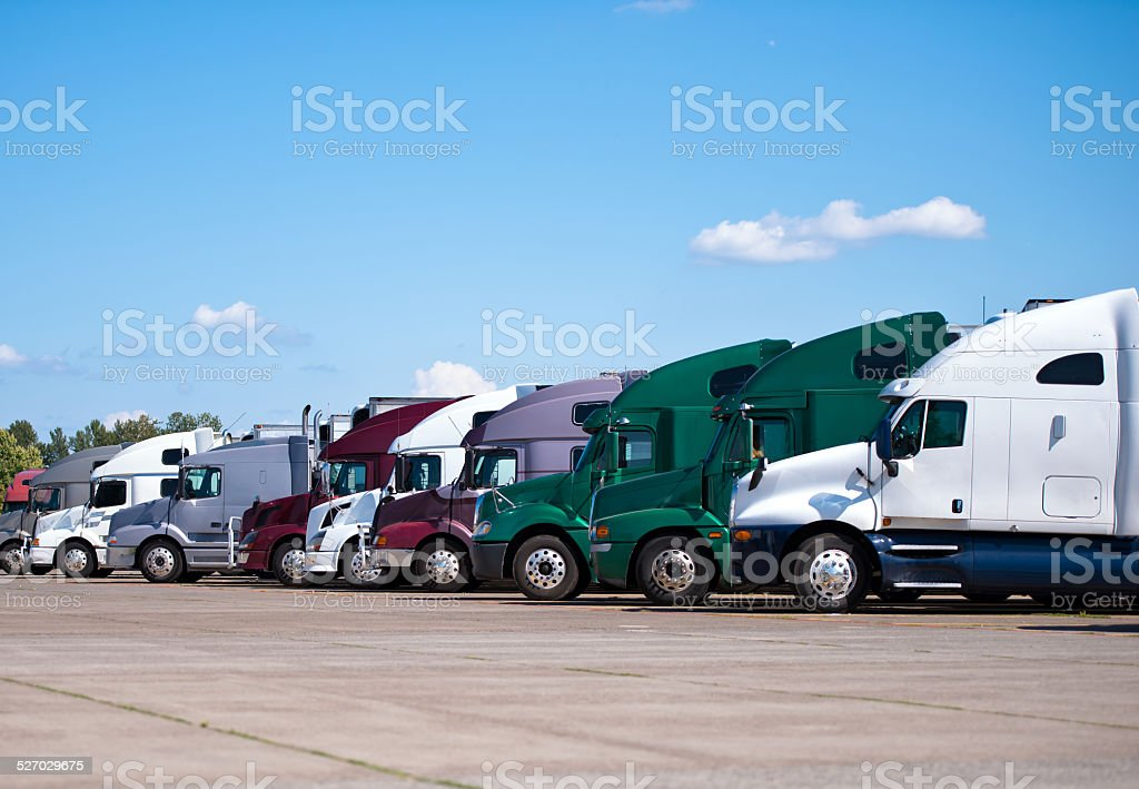 Semi trucks lined up on truck stop classic and modern stock photo