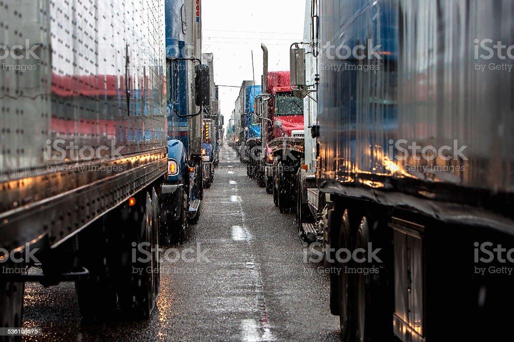 semi trucks lineup on a highway stock photo