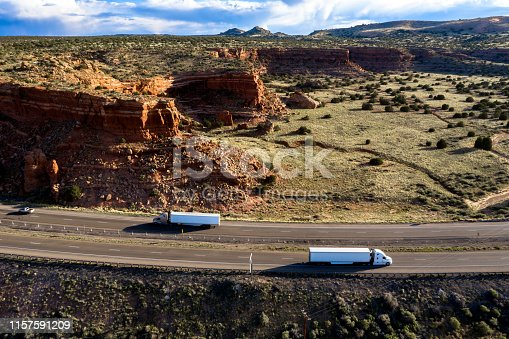 Semi trucks on Interstate 40 passing a large rock formation, aerial view, New Mexico, USA.