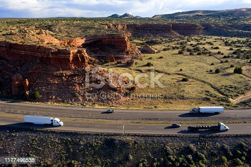 Semi trucks on scenic Interstate 40 near a large rock formations, New Mexico, USA.