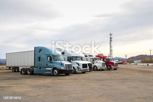 Row of Semi Trucks parked at a road side truck stop in the desert of California.