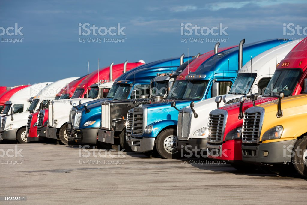 Large group of semi trucks parked at truck stop, American transport...