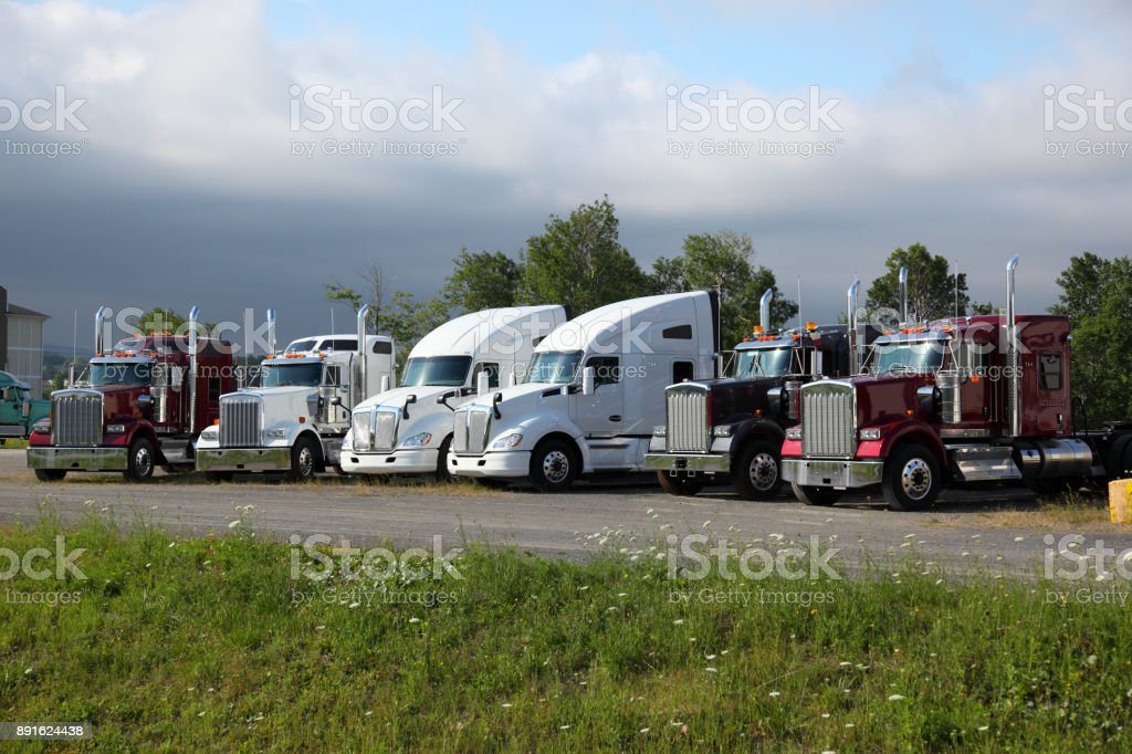 Semi trucks parked in a parking lot stock photo