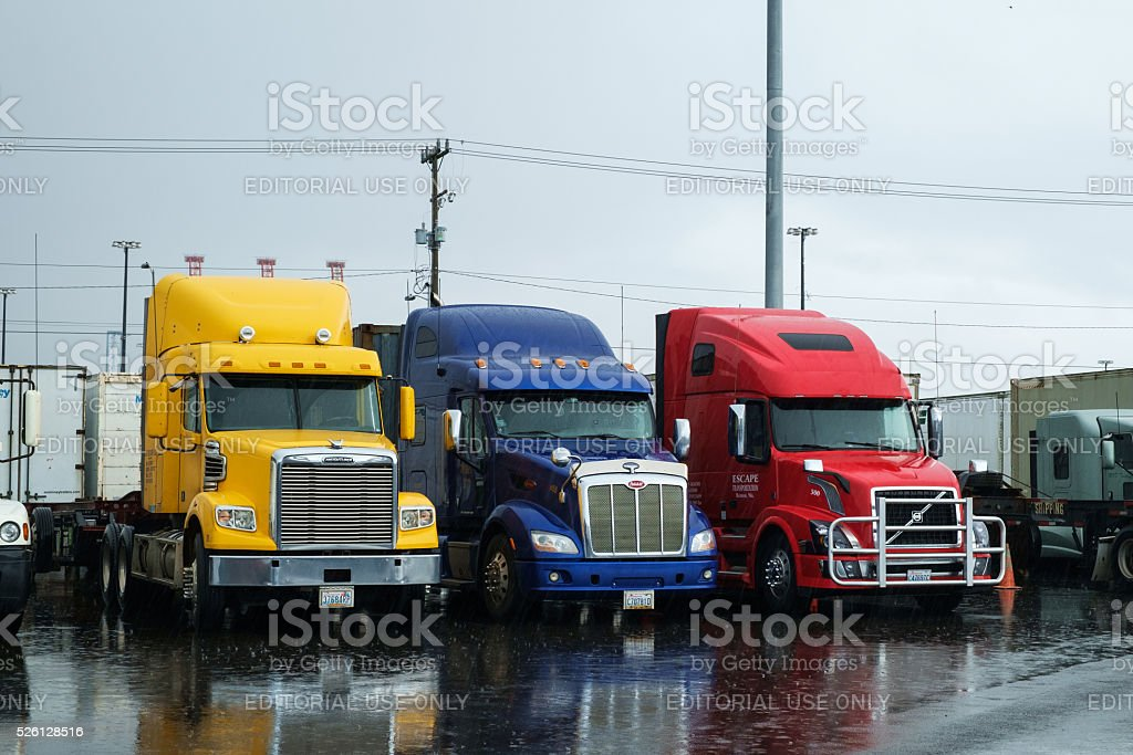 Semi trucks parked in rain stock photo