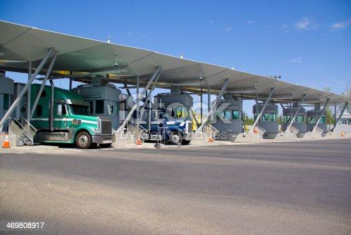 istock Semi trucks pay at tollbooth at Canadian border 469808917