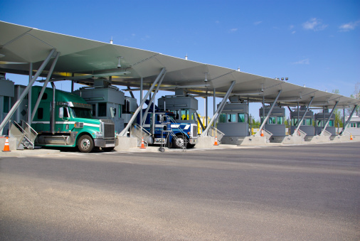 Semi Trucks Pay At Tollbooth At Canadian Border Stock Photo - Download Image Now