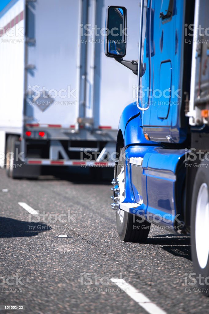 Semi trucks with trailers going in convoy on the road stock photo