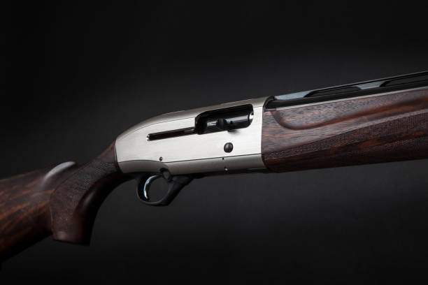 semi-automatic shotgun with a wooden butt and forearm on black back