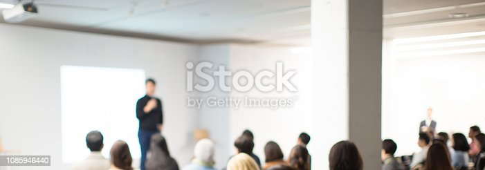 istock Seminar Audience in Training Room Watch Presentation. Speaker in Meeting at Business Event. Expert Presenter Giving Talk with Young Group of People. Rear View of Audience People Who Listen to Speaker. 1085946440