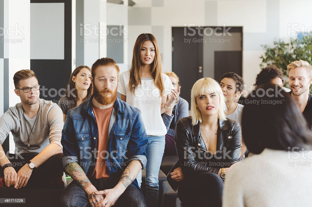Seminar for students, young asian woman asking question Large group of multi ethnic students attending a seminar at the university, talking with their teacher. Young asian woman asking question. 2015 Stock Photo