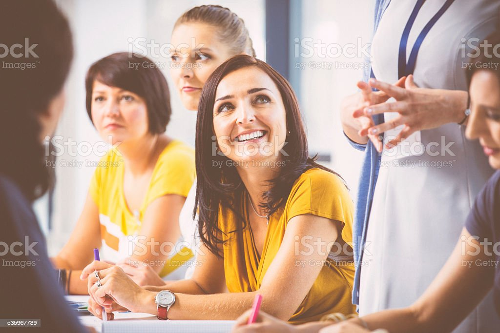 Seminar for woman Group of women attending a training, working together and discussing. Focus on a smiling attractive brunette wearing yellow dress. 2015 Stock Photo
