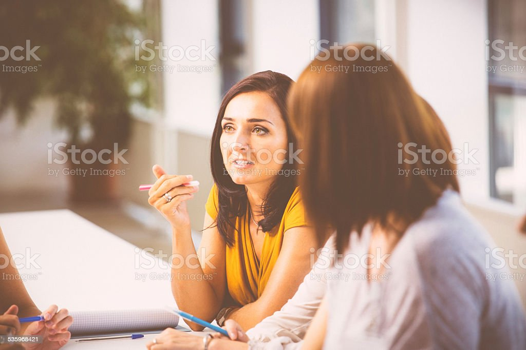 Seminar for woman Group of women brainstorming, working together and discussing. Focus on a smiling attractive brunette wearing yellow dress. 2015 Stock Photo