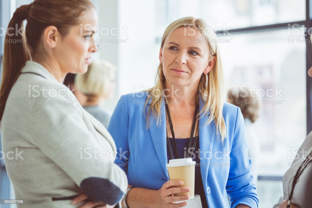 Seminar for woman, women discussing during coffee break Women discussing during coffee break at conference. Adult Stock Photo