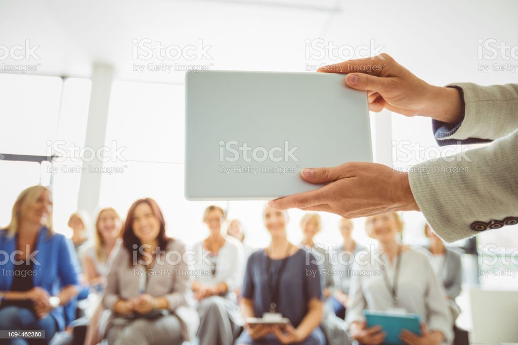 Seminar for women Speaker showing a digital tablet to group of businesswoman at seminar. Female hand with tablet computer against defocused group of women. Adult Stock Photo