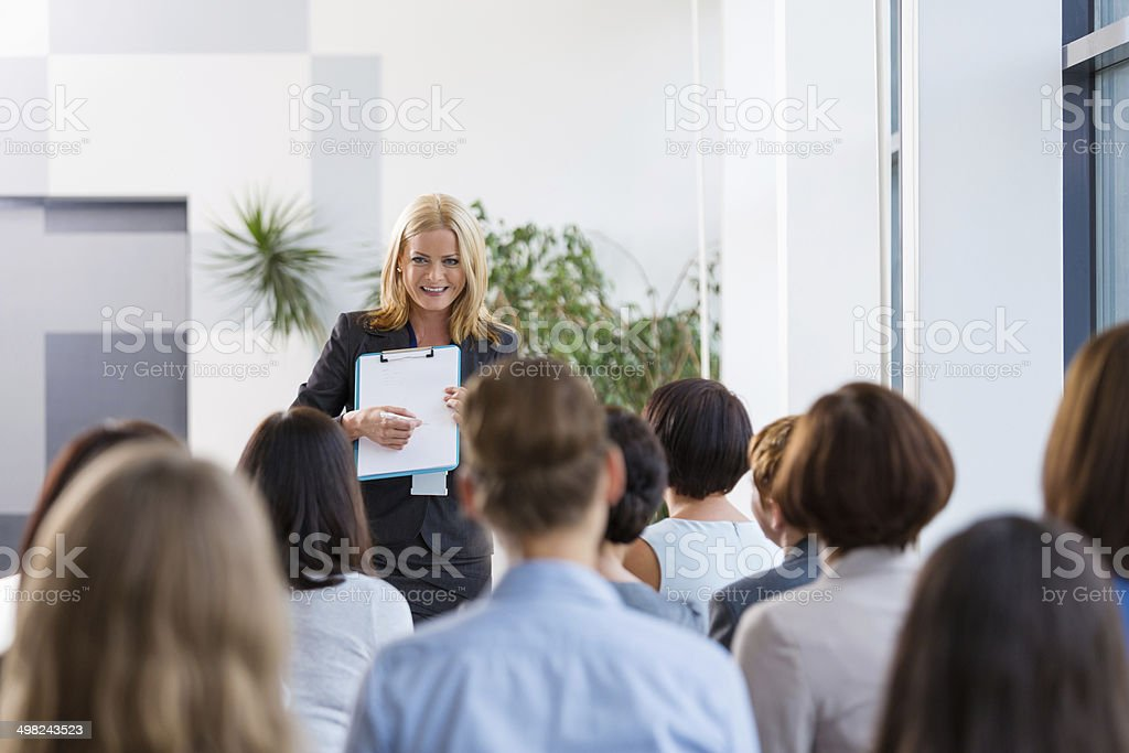 Seminar for women Group of businesswomen attending a seminar. Focus on the smiling female coach holding clipboard. 30-39 Years Stock Photo