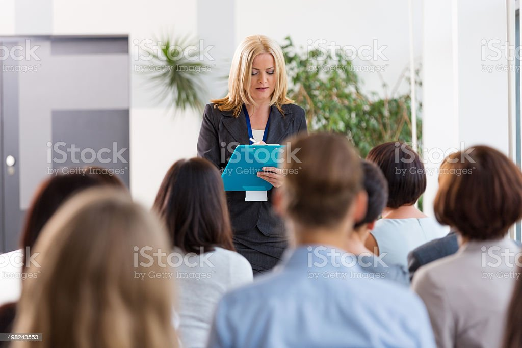 Seminar for women Group of businesswomen attending a seminar. Focus on the female coach taking notes. 30-39 Years Stock Photo