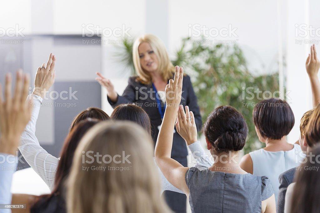 Seminar for women Group of businesswomen attending a seminar, raising their hands.  30-39 Years Stock Photo