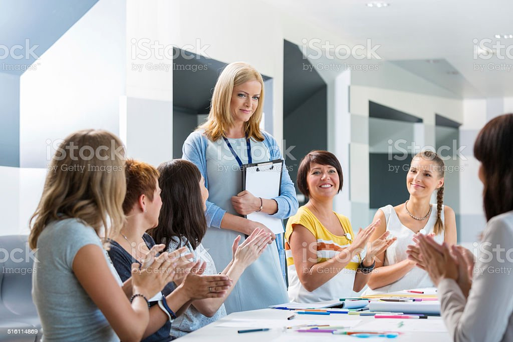 Seminar for women Group of women attending a training, looking at the female teacher and capping hands. Adult Stock Photo