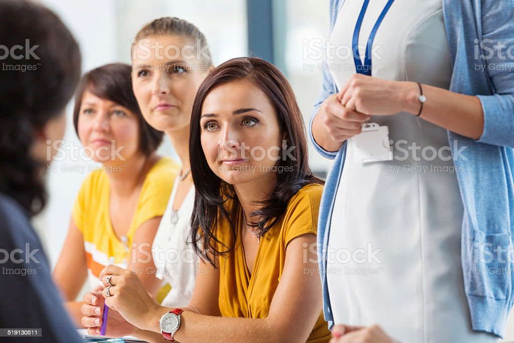 Seminar for women Group of adult women attending a semiar. Focus on the beautiful brunette. 30-39 Years Stock Photo