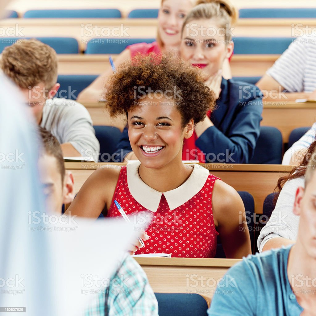 Seminar in lecture hall Group of students sitting in the lecture hall at university and listening to their teacher. Focus on the scheerful young woman. 20-24 Years Stock Photo