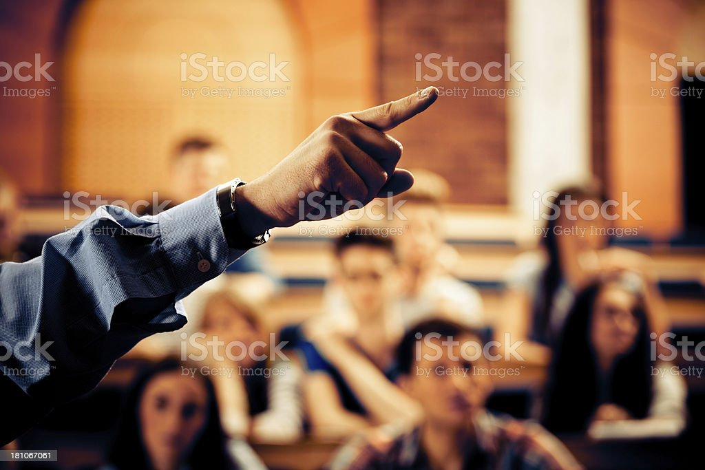 Seminar in lecure hall Large group of students sitting in the lecture hall at university and listening to their teacher. Focus on the professor's hand pointing. 20-24 Years Stock Photo