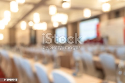 1158085965 istock photo Seminar or town hall meeting blur background in hotel conference room with audiences and speaker podium stage with presentation screen for entrepreneurship business speech or community talk discussion 1148939143