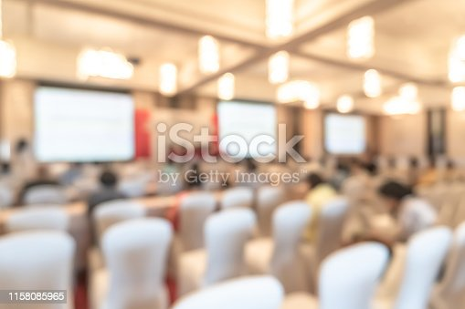 1158085965 istock photo Seminar or town hall meeting blur background in hotel conference room with audiences and speaker podium stage with presentation screen for entrepreneurship business speech or community talk discussion 1158085965